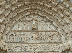 The tympanum over the central portal, with the Archangel Michael holding scales to judge the saved and the damned.